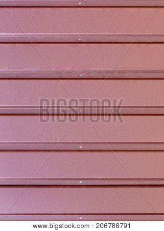 Reddish-brown metal fence made of corrugated steel sheet with gorizontal guides and metal rivets in the middle. Corrugated reddish-brown iron sheet background close up.