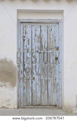 Old blue door on white house in the village of Belmonte province of Cuenca Spain.