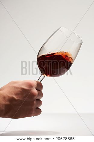Test red wine isolated on white background. Hand hold wine glass. Winery background