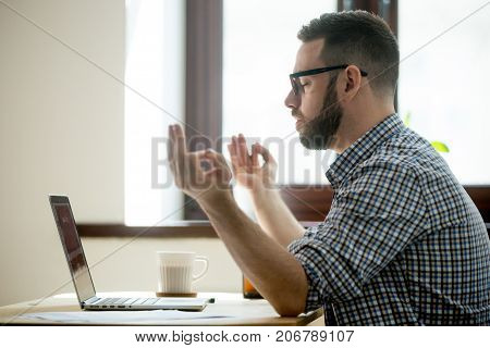 Young adult employee meditating  with hands in zen position, sitting in his office chair. Breathing exercise to build up concentration, cope with stress. Stress free life, mindful lifestyle concept
