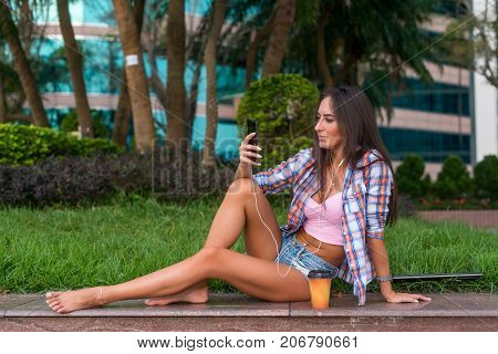 Happy beautiful young woman with bare legs sitting on stone curb in the park and listening to music in headphones