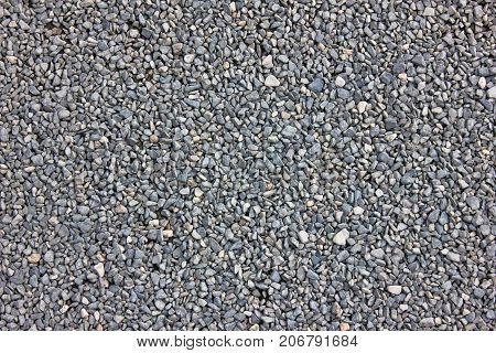 Texture of gray gravel. Grey stony floor. A wall of gray gravel. Stones small and medium-sized. Sharp edges of the stones. Sand and stones on the floor. The land is covered with stones
