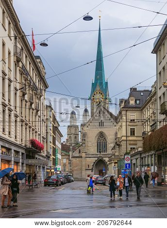Zurich, Switzerland - 30 September, 2017: view along Poststrasse street on a rainy evening, people on the street, towers of the Fraumunster and Grossmunster cathedrals in the background. Zurich is the largest city in Switzerland.