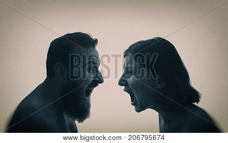 A man and a woman scream at each other. The concept of a family quarrel violence misunderstanding.