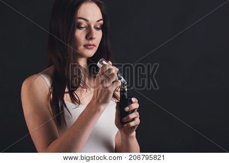 Trendy vaping gadget. Young brunette girl filling vape mod with fruit nicotine free e-liquid at black background, studio shot. Modern device for smokers, copy space