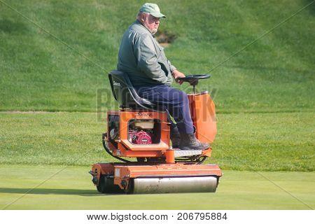 Zhytomyr Ukraine - May 12 2016: Big fat man gardening grass with a brushcutter at golf field