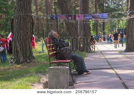 Zhytomyr Ukraine - May 05 2015: Homless old woman sleep on the bench at park