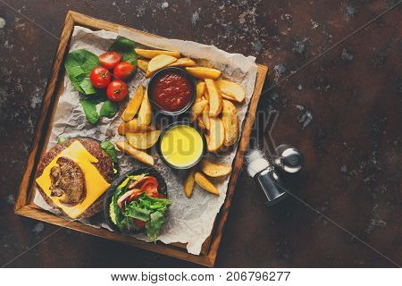Take away burger menu on wooden tray at old rusty background, top view. Black bun cheeseburger with baked potato wedges and sauces set, fast food concept