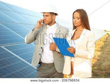 Engineers discussing project on installation of solar panels outdoors