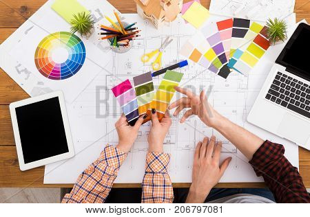 Interior designers teamwork with pantone swatch and house building plans on office desk, architects working with color palette, top view, mockup
