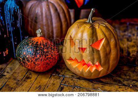 Group of Halloween pumpkin head jack lantern near candlestick bottles on black leather armchair background.