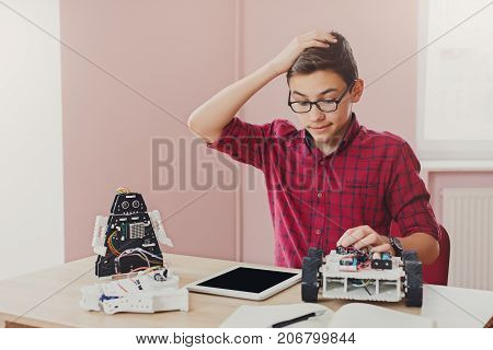 Stem education. Embarrassed boy made mistake while creating robot at lab, looking at blank tablet screen. Early development, diy, innovation, modern technology concept