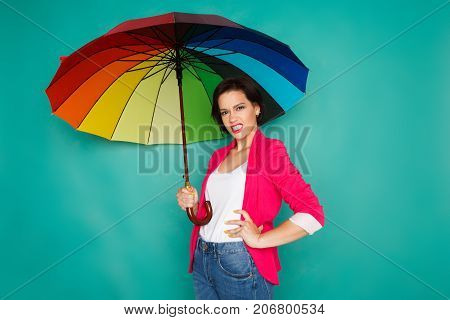 Agressive stylish girl in bright casual clothes under rainbow colored umbrella posing at azur studio background, copy space
