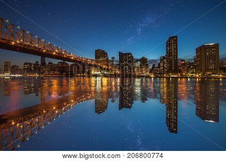 Manhattan panorama at dusk as seen from Roosevelt Island in New York USA. New York night scene with East River waterfront illuminated buildings and starry sky with milkyway.