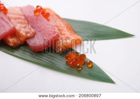 Tradional japanese food isolated at white background. Restaurant serving of fresh raw salmon, tuna and eel on bamboo leaf. Asian meals delivery