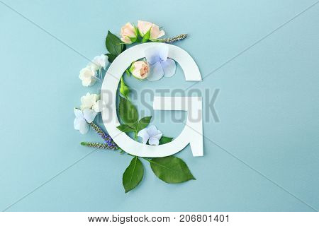 Composition with letter G and beautiful flowers on color background
