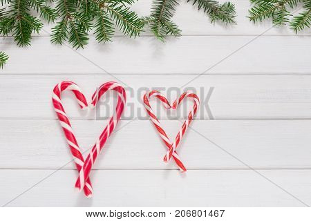 Sweet christmas background. Traditional candy canes form hearts on white wooden surface with fir tree branches border. Xmas or valentine day concept with copy space, top view