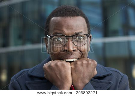 Close Up Portrait Of Scared African American Businessman Keeping Hands In Fists, Holding Them In Fro