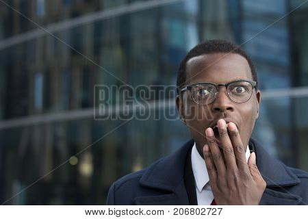 Astonished Bug-eyed Dark-skinned Businessman Wearing Suit, Covering His Mouth With One Hand, Looking