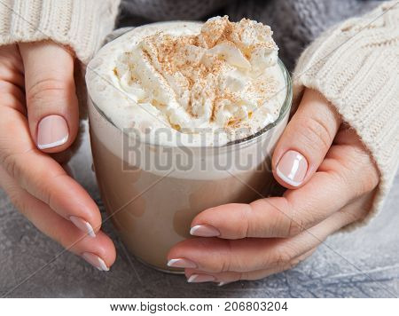 woman hands in a sweater with coffee latte on a table