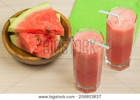 Watermelon juice in two glass tumblers with straw on a light wooden background, a delicious cocktail, a plate with slices of ripe watermelon on the table with a green cloth