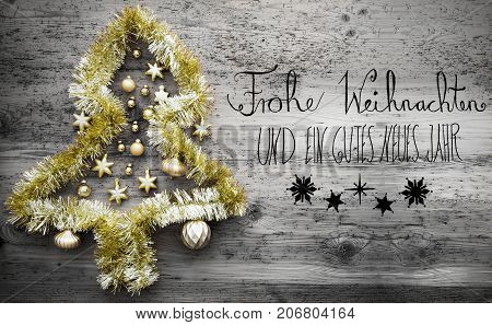 Black Calligraphy With German Text Frohe Weihnachten Und Ein Gutes Neues Jahr Means Merry Christmas And Happy New Year. Golden Tinsel Christmas Tree. Christmas Ball Ornament On Gray Wooden Background