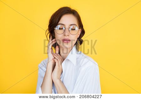 Charming brunette young woman in glasses wearing white shirt touching hair with eyes closed posing.