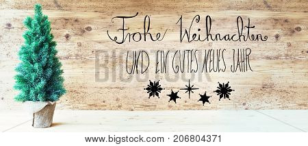 Calligraphy With German Text Frohe Weihnachten Und Ein Gutes Neues Jahr Means Merry Christmas And Happy New Year. Green Christmas Tree With Rustic Brown Wooden Background.