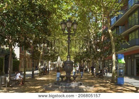 HOSPITALET DE LLOBREGAT, SPAIN - SEPTEMBER 2, 2017: A view of the Rambla Just Oliveras promenade in Hospitalet de Llobregat, Spain, the main pedestrian street in the Hospitalet Centre district