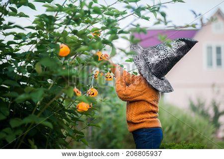 Adorable smiling toddler girl decorating garden for halloween with jack-o-lantern garland.