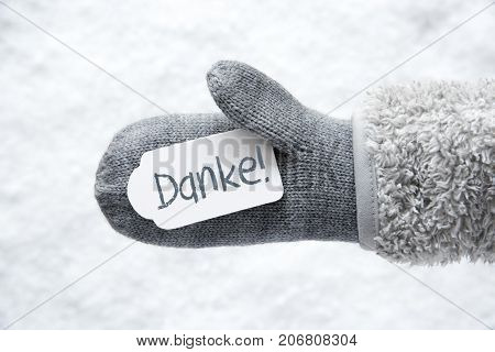 Wool Glove With Label With German Text Danke Means Thank You. White Snow Background.