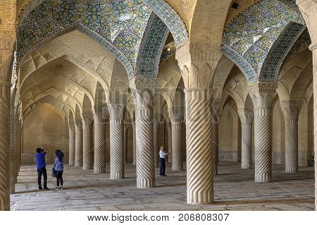 Fars Province Shiraz Iran - 19 april 2017: Tourists photograph the interior of the prayer hall in Vakil Mosque.