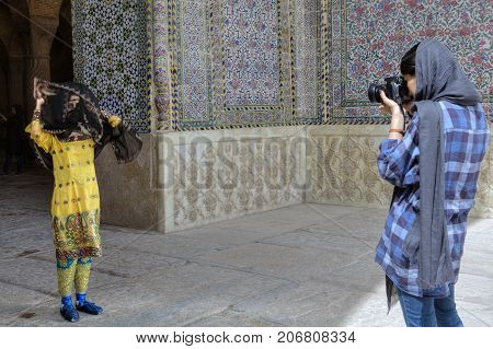 Fars Province Shiraz Iran - 19 april 2017: The girl photographer photographs a model in a national Iranian suit near the entrance to the mosque.