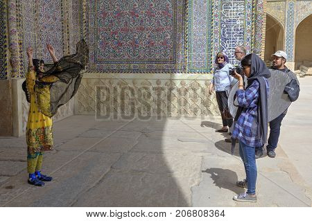 Fars Province Shiraz Iran - 19 april 2017: A photo shoot in the open air next to a mosque a woman in a national Iranian costume is photographed by a woman photographer.