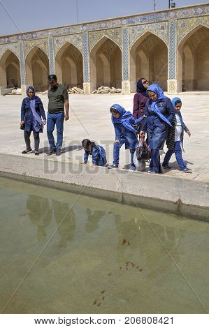 Fars Province Shiraz Iran - 19 april 2017: Several Iranian tourists watch the goldfish swimming in the puddle in the courtyard of the mosque.