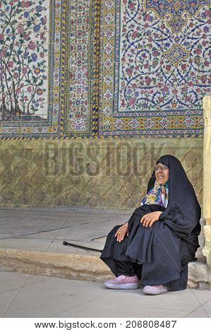 Fars Province Shiraz Iran - 19 april 2017: A woman pilgrim dressed in Islamic clothing sits in a holy place.