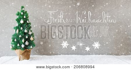 Calligraphy With German Text Frohe Weihnachten Und Ein Gutes Neues Jahr Means Merry Christmas And Happy New Year. Christmas Tree With Silver Christmas Ball Ornament On Snow With Snowflakes.