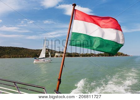 Lake Balaton v from a ship deck with the Hungarian flag and a sailboat in Hungary