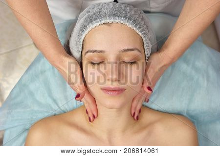 Top view of face massage. Hands of cosmetician, young woman. How to relieve facial stress. poster