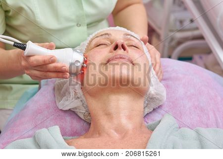 Adult woman, rf skin tightening. Mature female at the cosmetologist. Information on aesthetic medicine.