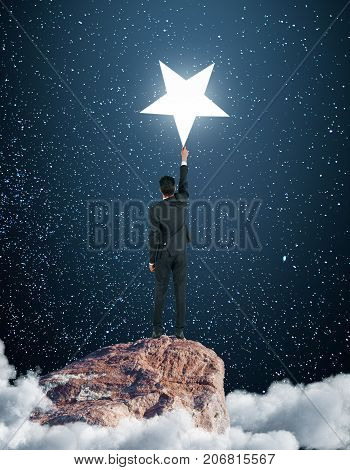 Back view of young businessman on cloudy mountain top reaching bright star. Goal concept