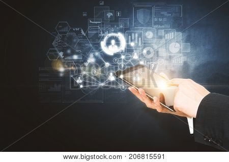 Side view and close up of businessman hands using tablet with digital business hologram on dark background. Device and future concept. Double exposure