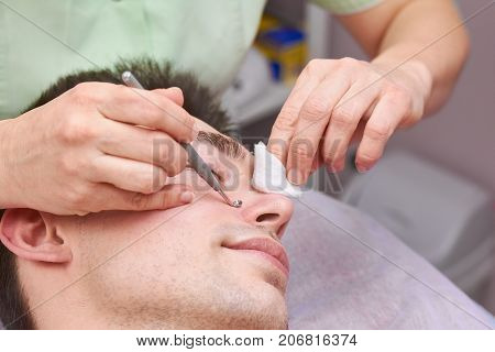 Young man having face cleaned. Hands with blackhead remover.