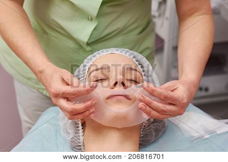 Hands of cosmetician, collagen mask. Face of cosmetology clinic customer.