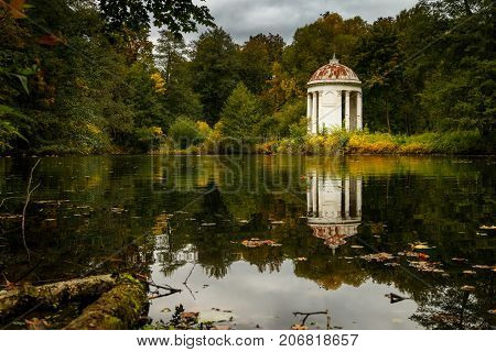 Classical white rotunda on the shore of a pond. Autumn Park. An ancient graceful rotunda with columns. Autumn landscape with forest, pond and architecture.