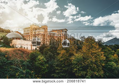 Cableway in resort district of Sochi city with hotel building in background two modern funicular cabins and mountains behind sunny autumn day Russia