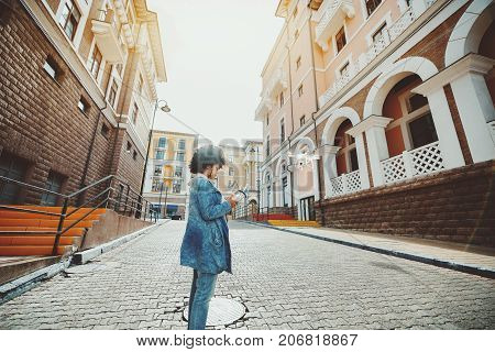 Biracial young woman with curly hair is standing on pavement stones of empty urban street and operating white flying drone using remote device with screen joystick and antennas; sunny autumn day