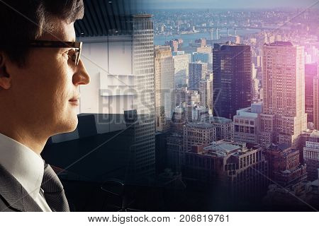 Side view of attractive young businessman on abstract city and office background. Occupation concept. Double exposure