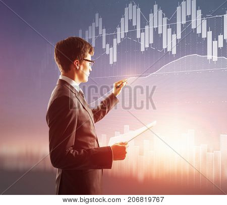 Side view of young businessman with document in hand drawing abstract forex diagram on blurry background. Trading concept. Double exposure