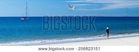 Lady fishing on a tropical pristine white sandy beach Looking out to sea at Hervy Bay from Frazer Island's North West Coast with a distant cruising yacht near the ocean horizon and a seagull in full flight.